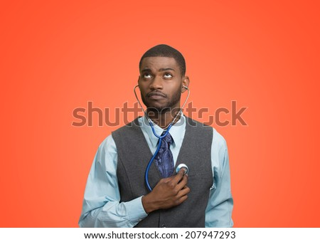 Closeup portrait executive man, business person, worker listening to his heart with stethoscope looking up isolated red background. Preventive medicine, financial condition concept. Face expression - stock photo