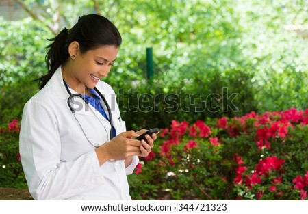 Closeup portrait, friendly, young smiling confident female doctor with stethoscope, healthcare professional texting on phone, isolated outside green trees, red flowers background. Positive emotion - stock photo