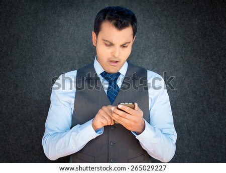 Closeup portrait, funny young man in vest and blue tie, shocked surprised, wide open mouth, by what he sees on his cell phone, isolated gray black background. - stock photo