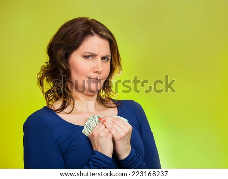 Closeup portrait greedy middle aged woman corporate business employee, worker, student holding dollar banknotes tightly isolated green background. Negative human emotion facial expression feeling - stock photo