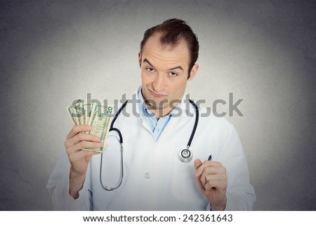 Closeup portrait grumpy greedy miserly health care professional, male doctor holding, protecting his money dollars in hand isolated grey wall background. Negative human emotions, facial expressions - stock photo