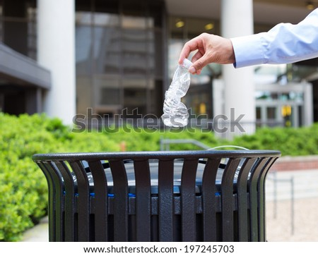 Closeup portrait, hand throwing plastic empty water bottle in recycling bin, isolated building and trees background - stock photo