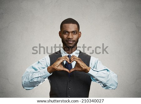 Closeup portrait handsome smiling young business man makes the heart using fingers, hands, isolated grey wall background. Positive human emotions, facial expressions, feelings, body language, attitude - stock photo