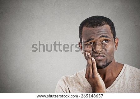 Closeup portrait handsome young man touching face having really bad pain tooth ache isolated gray wall background. Negative human emotions, facial expression feelings - stock photo