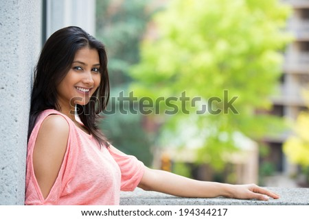 Closeup portrait, happy beautiful, smiling young woman in pink shirt, posing on outdoors balcony, isolated on background with trees, and buildings, city urban life - stock photo