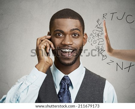 Closeup portrait happy business man talking on mobile phone, letters coming out of his free ear with hand pushing them back inside isolated grey wall background. Positive facial expressions, emotions - stock photo