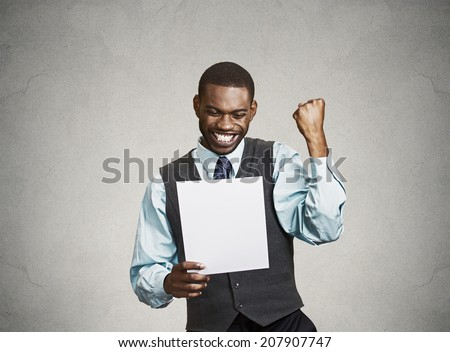 Closeup portrait happy excited young business man executive looking monthly statement glad to pay off bills isolated grey background. Positive emotion facial expression. Financial success good news - stock photo
