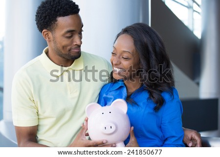 Closeup portrait, happy handsome couple or two business people holding pink piggy bank looking at each other, laughing.  Smart financial decisions - stock photo