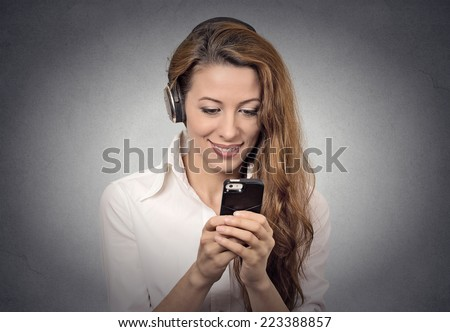 Closeup portrait happy looking, surprised businesswoman with headphones reading news, sms on smart phone holding mobile listening radio podcast isolated grey background. Human face expression, emotion - stock photo