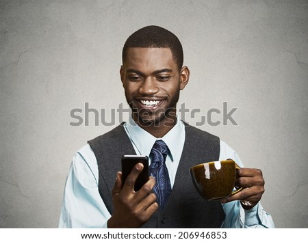 Closeup portrait happy, smiling business man reading good news on smart phone, lawyer holding mobile, drinking cup coffee isolated black background. Human face expression, emotion, corporate executive - stock photo