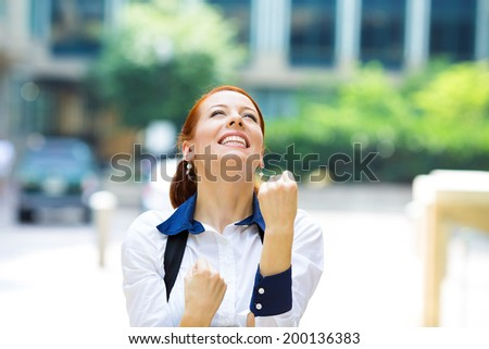 Closeup portrait happy smiling business woman with arms up, excited pumping fists, celebrating isolated background outdoors corporate office. Positive human emotion, facial expression feeling reaction - stock photo