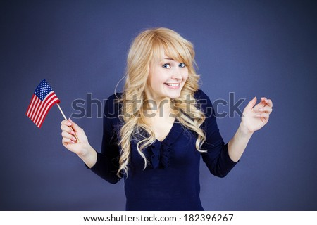 Closeup portrait happy, smiling excited blonde woman, employee, worker, student holding united states of america flag, USA, isolated dark blue background. Positive emotions, face expressions, attitude - stock photo