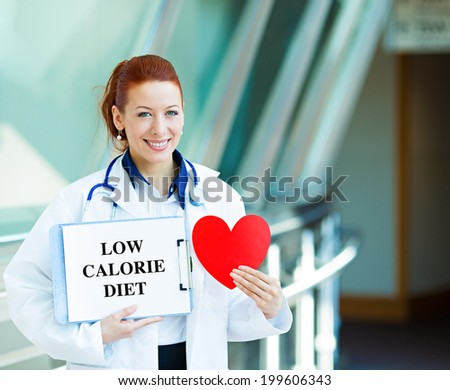 Closeup portrait happy smiling female health care professional woman family doctor, cardiologist with stethoscope holding sign low calorie diet heart isolated hospital hallway background. Patient plan - stock photo
