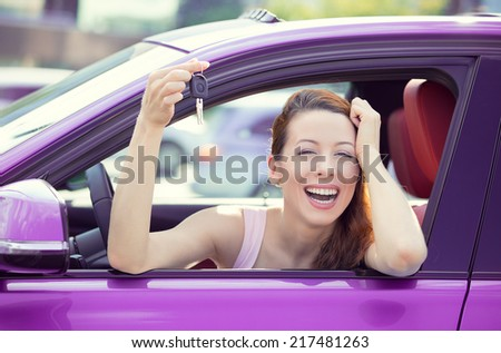 Closeup portrait happy, smiling, young attractive woman, buyer sitting in her new purple car showing keys isolated outside dealer, dealership lot office. Personal transportation, auto purchase concept - stock photo