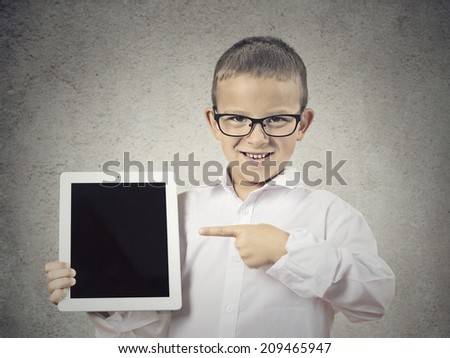 Closeup portrait happy, smiling young boy, child shows tablet with touchscreen display, pointing with finger isolated grey wall background. Positive facial expression, emotions. New generation gadgets - stock photo