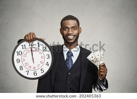Closeup portrait happy young business man, corporate employee, ceo, holding wall clock, dollar bills in hands. Time is money concept, isolated black, grey background. Positive emotions face expression - stock photo