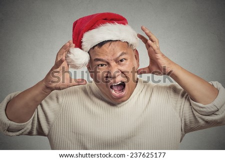 Closeup portrait headshot christmas man with red santa claus hat hands on head, stressed out, yelling, showing frustration. Negative human emotions face expression isolated on grey wall background - stock photo
