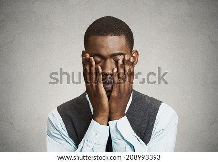 Closeup portrait, headshot Depressed young Man, isolated grey wall background. Negative human emotions, Facial Expressions, body language, life perception, feelings. Mental health concept - stock photo