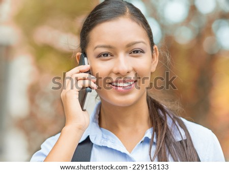 Closeup portrait headshot happy beautiful woman laughing smiling speaking on mobile phone isolated outdoors outside background with indian fall trees. Positive human face expression emotion feeling - stock photo