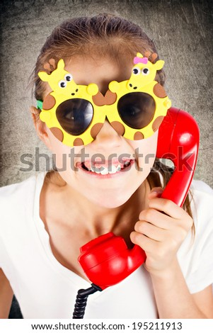 Closeup portrait, headshot happy, funny looking little girl with sun glasses speaking, talking on phone isolated black background. Positive human face expressions, emotions, feelings, life perception - stock photo