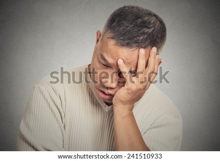 Closeup portrait headshot sad bothered stressed middle aged man holding head with hand really depressed about something isolated grey wall background. Negative human emotion facial expression feeling - stock photo