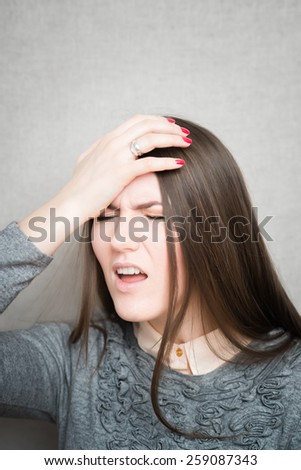 Closeup portrait headshot stressed sad young housewife, woman, employee having migraine, tension headache isolated on grey wall background. Human face expression emotion reaction, attitude - stock photo