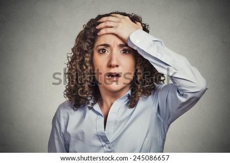 Closeup portrait headshot terrified young business woman looking shocked, surprised, full disbelief, hand on head isolated grey wall background. Negative emotion facial expression feeling reaction - stock photo