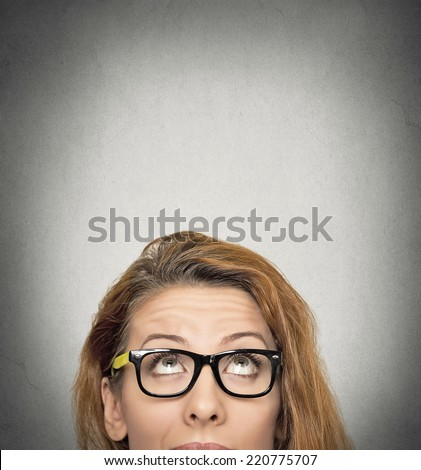 closeup portrait headshot woman looking up grey wall background with copy space above head. Human face expressions, emotions, feelings, body language - stock photo