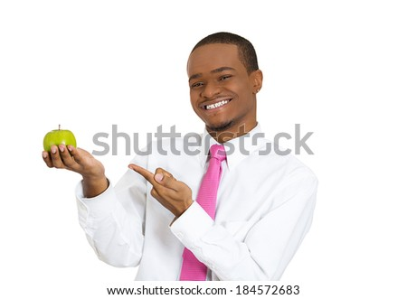 Closeup portrait, healthy, happy young man nutritionist, personal fitness trainer holding and offering an apple as a healthy alternative, isolated white background. Positive emotion facial expression - stock photo