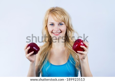 Closeup portrait, healthy young woman nutritionist, personal fitness trainer holding, offering apples, healthy alternative, isolated light blue background. Positive emotion facial expression - stock photo