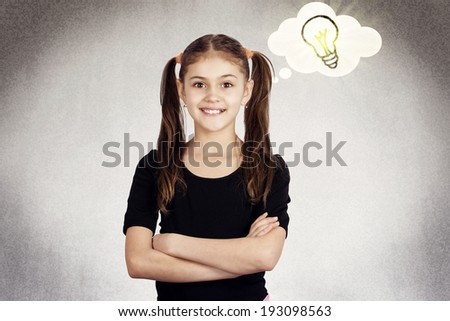 Closeup portrait intelligent, excited, little girl having idea, arms crossed isolated grey black background with lighting bulb. Positive human emotions facial expression, attitude, perception reaction - stock photo