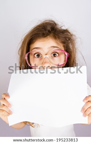Closeup portrait little girl with glasses looking surprised, scared, cautious, curious, hiding behind blank white paper, blank sign, space text looking at you isolated grey background. Face expression - stock photo