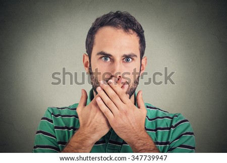Closeup portrait man with hand over his mouth, speechless, isolated on gray wall background - stock photo