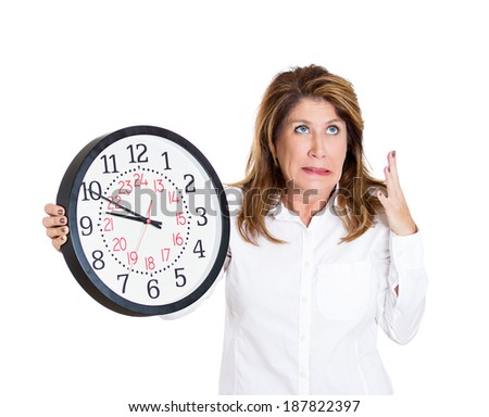 Closeup portrait mature, woman, worker, holding clock looking anxiously, pressured by lack, running out of time, isolated white background. Human face expression, emotion, reaction, corporate life - stock photo