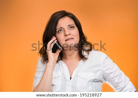 Closeup portrait middle aged angry business woman, corporate employee talking on cell phone, having unpleasant conversation, isolated orange background. Negative emotions, facial expressions, reaction - stock photo