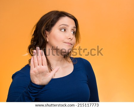 Closeup portrait middle aged, grumpy woman with bad attitude, giving talk to my hand gesture with palm outward, isolated orange background. Negative emotions, facial expression feelings, body language - stock photo