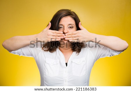 Closeup portrait middle aged woman covering closed mouth. Speak no evil concept, isolated yellow background. Negative human emotion facial expressions, sign, symbol. Media news coverup, censorship  - stock photo