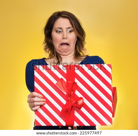 Closeup portrait middle aged woman opening gift box very upset at what she received, isolated yellow background. Negative human emotion, facial expression. Unsuccessful holiday shopping concept - stock photo