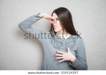 Closeup portrait middle aged woman who covers, pinches her nose with hand looks with disgust, something stinks, bad smell, situation. Human face expressions, body language - stock photo