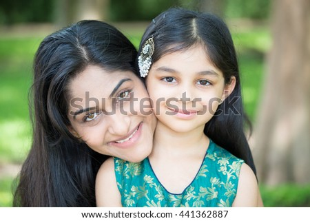 Closeup portrait, mom enjoying time with daughter, isolated outside green trees background - stock photo