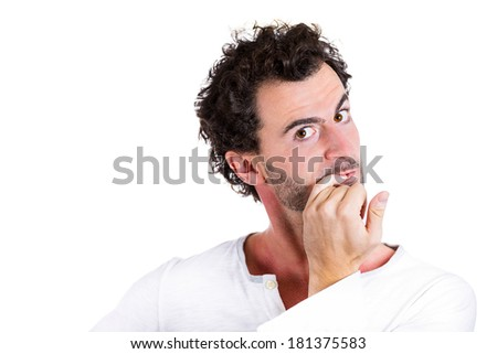 Closeup portrait nerdy, shy, confused young guy, scared, shocked, restless man biting his nails looking at you with craving for something isolated white background. Human emotions, facial expressions - stock photo