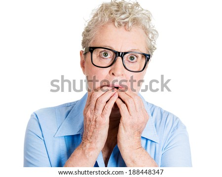 Closeup portrait nervous nerd, senior mature woman in black glasses, bite fingernails craving something, anxious, isolated white background. Negative human emotion, facial expression, feeling reaction - stock photo