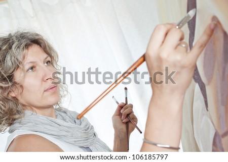 Closeup portrait of a beautiful artist, painter. - stock photo