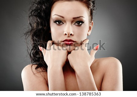 Closeup portrait of a beautiful brunette posing on gray background - stock photo
