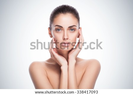closeup portrait of a beautiful female model with her hands near face - isolated on blue gradient background - stock photo