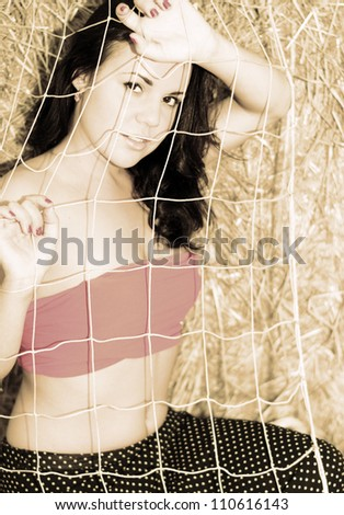 Closeup portrait of a beautiful girl behind grid. Toned image - stock photo