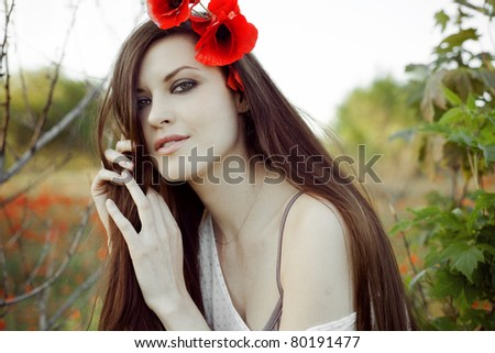 Closeup portrait of a beautiful girl with poppies in her hair - stock photo