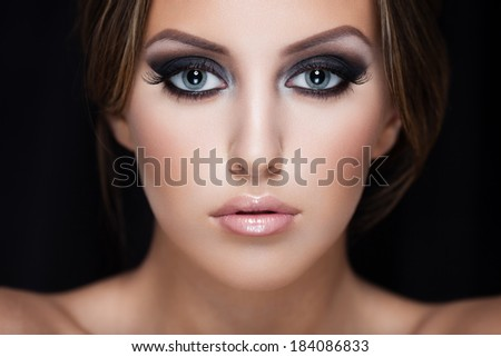 Closeup portrait of a beautiful lady on black - stock photo
