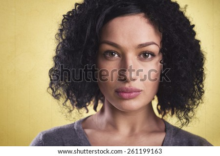 Closeup portrait of a beautiful latina woman with dark skin looking serious, isolated on yellow background. - stock photo