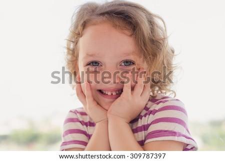 Closeup portrait of a beautiful little girl smiling near the window - stock photo